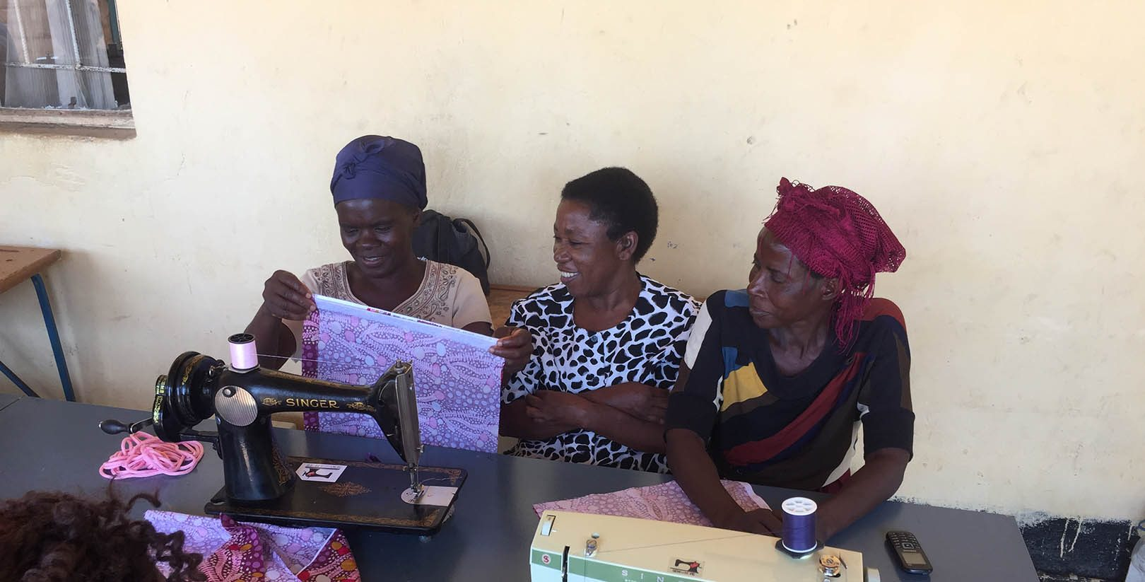 Women in Zambia learning on their new sewing machine donated by Sew Much Hope